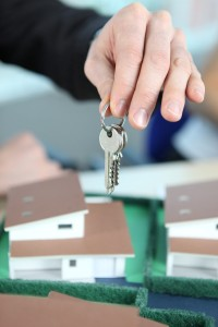 Image of a hand holding doorkeys over a model house