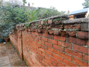 Red brick wall, crumbling at the top
