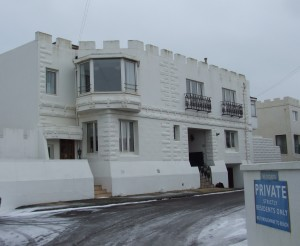 Western Esplanade seafront property in Hove in the snow. White building with castellated walls.