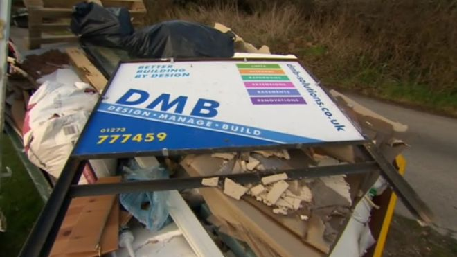 DMB Solutions (building firm) sign lying discarded on a heap of rubble